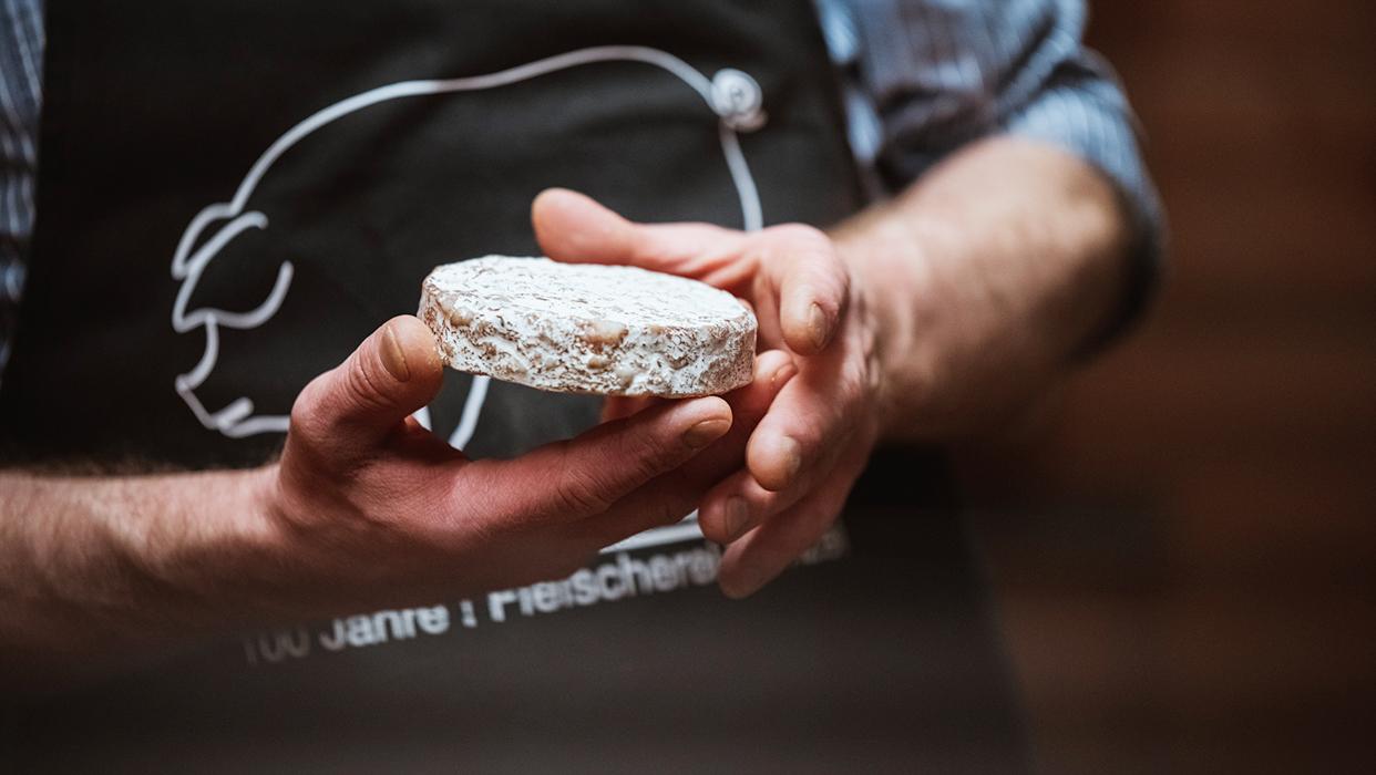 Fleischermeister Christian Wenzel hält eine Frikadelle in der Hand.