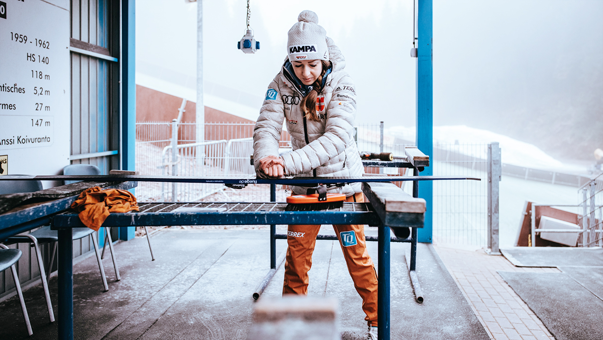 Skispringerin Julia Seyfarth präpariert ihren Skier für das Training.