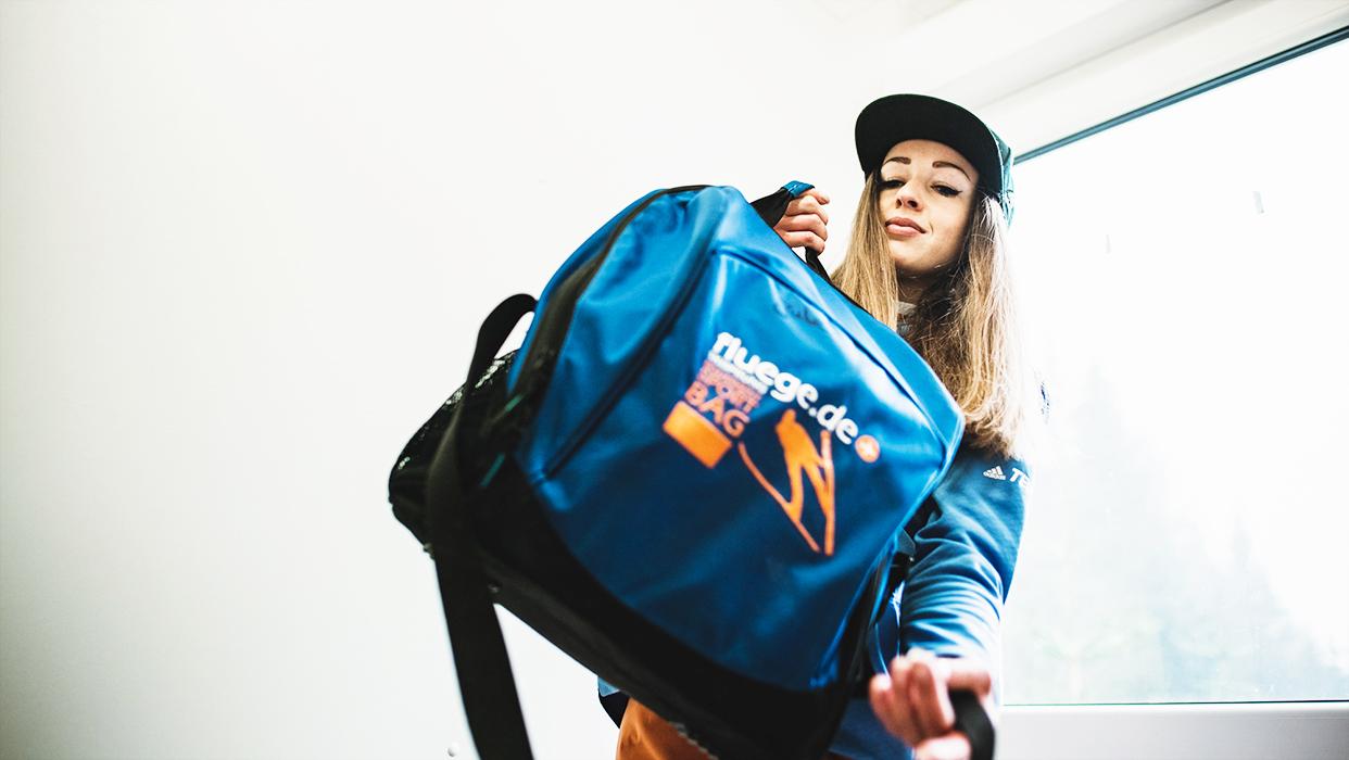 Skispringerin Julia Seyfarth mit Mütze und Sporttasche.