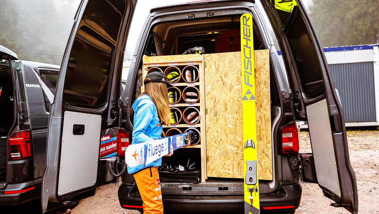 Skispringerin Julia Seyfarth packt ihre Skier in einen Transporter.