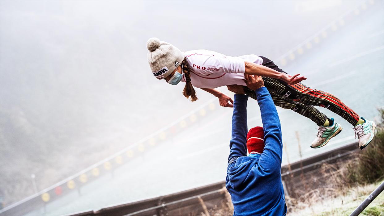 Trockenübung: Ein Trainer hebt eine Nachwuchsskipringerin hoch und übt die Haltung für den Sprung.